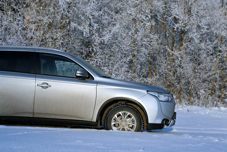 outlander: Modern crossover with high clearance to snow-covered field on a sunny day