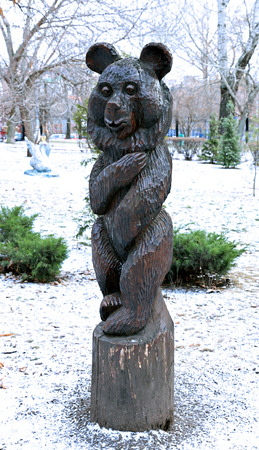 modest: MOSCOW, RUSSIA - DECEMBER 22, 2014: Modest wooden bear sculpture in a Presnensky park in Moscow