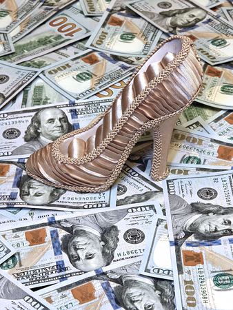 stockpiling: Womens shoe on a background of plurality of US dollars bills Stock Photo