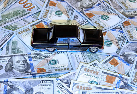 bribes: Black car on stack of American dollars Stock Photo