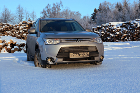 outlander: ZVENIGOROD, RUSSIA - DECEMBER 30, 2014: Silver Mitsubishi Outlander car on the snow field on a background of harvested tree trunks
