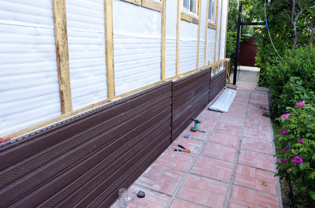 wall covering: Installation of brown plastic siding on the facade of the house