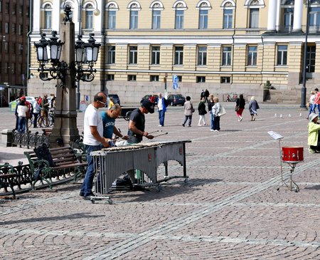 listeners: HELSINKI, FINLAND - JULY 7, 2015: Street musicians are playing on the xylophone on the Senate Square in Helsinki