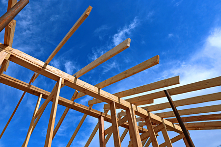wooden joists: Installation of wooden beams at construction the roof truss system of the frame house