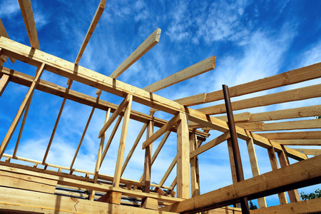 roofing system: Installation of wooden beams at construction of the frame house