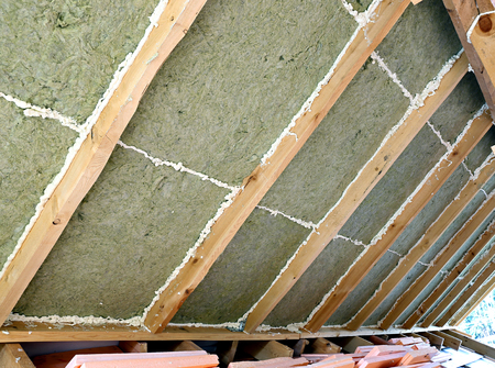 wooden joists: Laying slabs of heat insulation material between beams in the construction of roof in the frame house Stock Photo