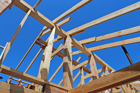 roof framework: Installation of wooden beams at construction of the frame house