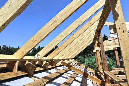 outbuilding: Installation of wooden beams at construction the roof truss system of the frame house