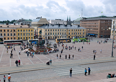 senate: HELSINKI, FINLAND - JULY 7, 2015: Many tourists and tour buses around the monument to Russian Emperor Alexander II on the Senate Square in Helsinki Editorial