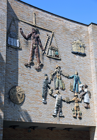 stucco facade: HELSINKI, FINLAND – JULY 9, 2015: Facade Aalto University School of Business in Helsinki with the artistic stucco figures of people of different nationalities Editorial