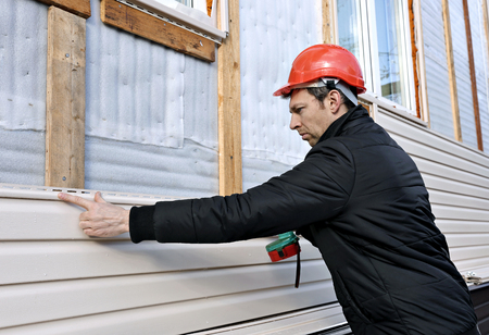 A worker installs panels beige siding on the facade of the house Stok Fotoğraf
