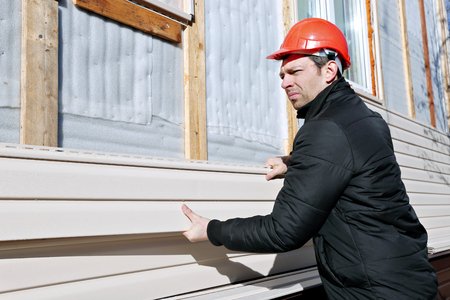 sheathing: A worker installs panels beige siding on the facade of the house Stock Photo
