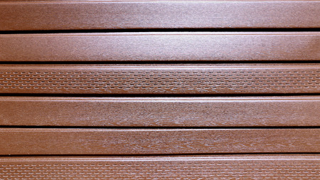 soffit cladding: The texture of brown plastic siding