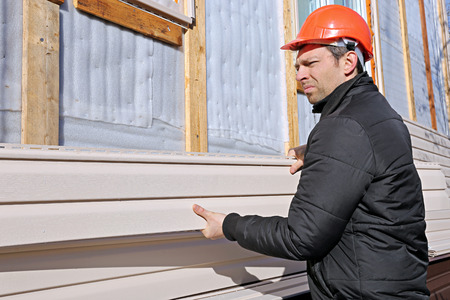 A worker installs panels beige siding on the facade of the house Фото со стока