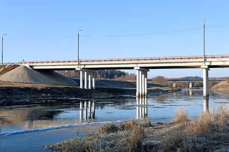 struts: The long bridge on piles over the river and floating of ice on the river in early spring