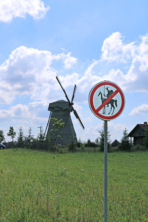 banned: DUDUTKI, BELARUS - JULY 17, 2014: Old windmill and road sign to Don Quixote passage banned in Dudutki, Belarus