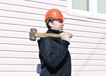Worker with big sledge hammer on the shoulder at the construction site