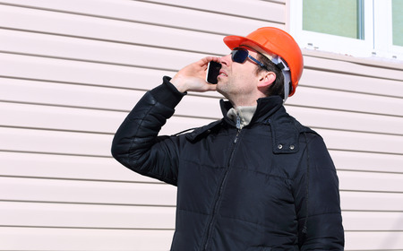 supervise: Worker in an orange helmet on a construction site in winter talking on smartphone Stock Photo