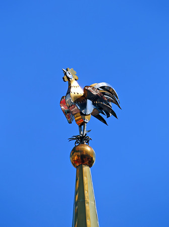 vane: Weathervane in the form of a golden rooster on the spire tall tower Stock Photo