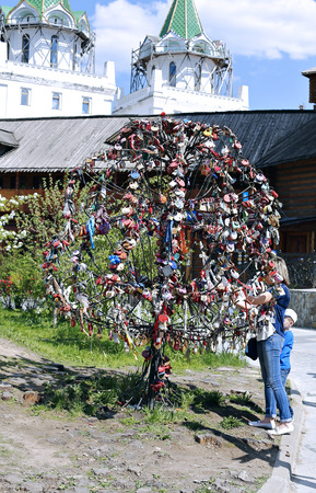 commemorative: MOSCOW, RUSSIA - MAY 7, 2016: Girl attaches a commemorative ribbon on iron decorative wedding tree Editorial
