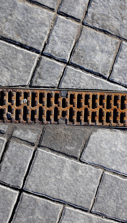 gutter: Gutter drainage, covered with steel lattice on the road Stock Photo