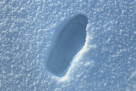 dint: Footprint of big male shoes on snow