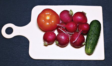 Fresh vegetables for salad on a cutting board on a dark background