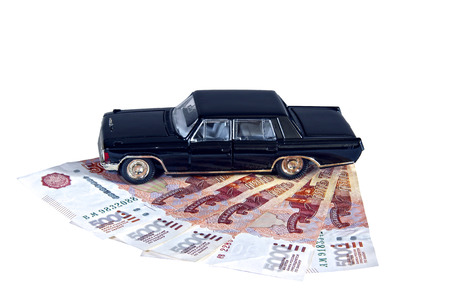Model of a black car on Russian banknotes isolated on a white background