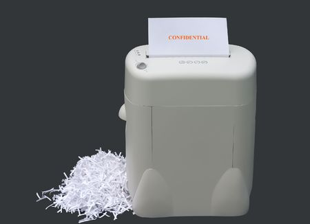 confidential information being shredded with a pile of shredded paper infront of shredder