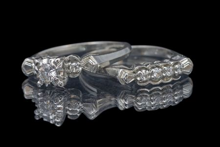 close up of wedding and engagement rings on reflective surface