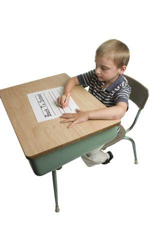 白い背景上に分離されて学校の机の上の学校への書き戻しの少年 写真素材