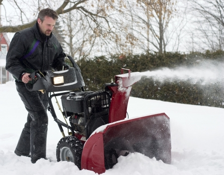 man operating snow blower in winter