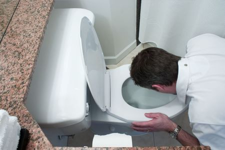 man kneeling by toilet bowl and throwing up Stock Photo