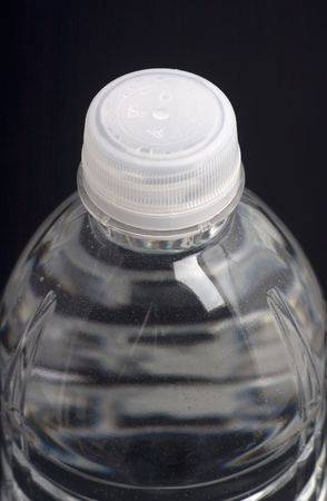 purified: close-up of a plastic water bottle on black background
