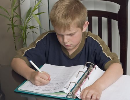 Boy doing homework sitting at a dining table