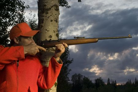 hunter leaning on tree and aiming rifle Stock Photo