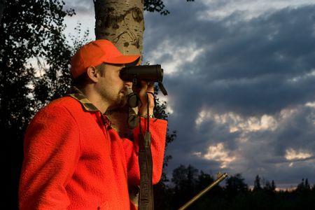 zichtbaarheid: jager in hoge zichtbaarheid kleding kijken door een verrekijker Stockfoto