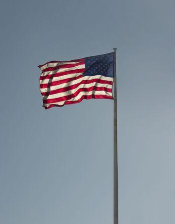 backlit US flag on blue sky Imagens