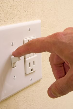 closeup of hand turning off light switch