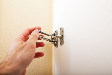 close up of hand locking the swing arm security latch in a hotel room