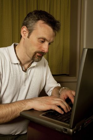 close up of man typing on a laptop in a hotel room Stock Photo - 10206077