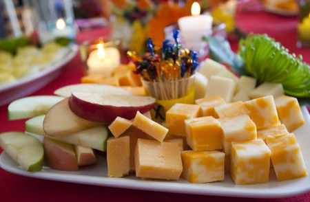 cheddar: cheddar cheese and sliced apples on a platter with decorative flowers and candles