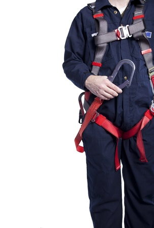 worker wearing blue coveralls and a fall protection harness and lanyard for work at heights photo