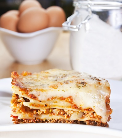 close up of meat lasagna with flour and eggs in the background