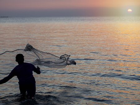 Men are casting in the sea at sunrise to sunset.