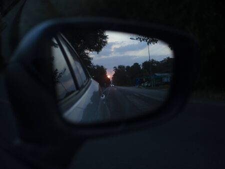 The sun sends light in the sideview mirror of a car