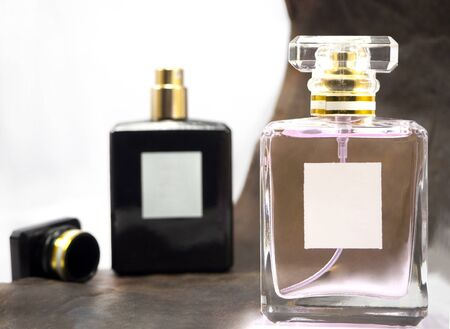 Black and pink perfume bottle On a white background with brown leather.Perfume is made of essential oils with an alcohol solution.Floral scents are derived from natural or synthetic scents are mixed up.Apply or spray on your clothes or body.Perfume evaporates out with the fragrant smell I sniffed out some odor has caused many bringing flowers mixed together Stock fotó