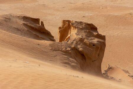 Die Sanddünen mit wehendem Sand während eines Sandsturms über den Boden.