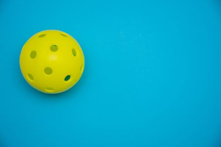 Bright yellow pickleball or whiffle ball on a solid bright blue flat lay background symbolizing sports and activity with copy space.