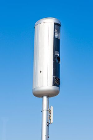 Traffic speed camera on a blue sky background preparing to use technology to stop speeding in cars on the road 스톡 콘텐츠